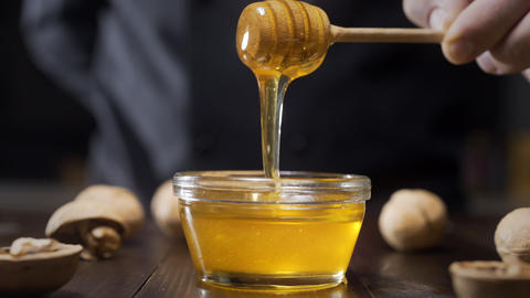 Chef dips wooden honey stick to the glass bowl with liquid honey, cooking with Footage