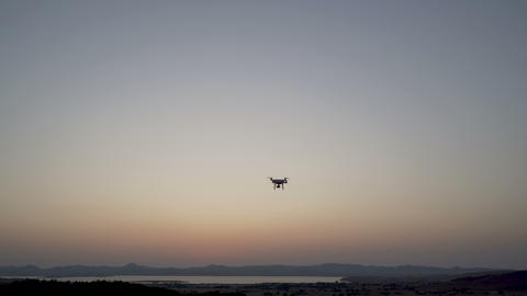 Black quadcopter drone landing after filming sea coast Live Action