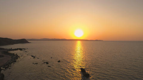 Scenic Sundown aerial view above calm sea near rocky coast in Greece Live Action