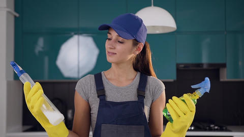 Young smiling woman from cleaning service comparing two spray cleaning agents in Live Action