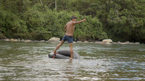 An Indigenous Boy Falls Into A Water From A Floating Tire In Ecuador Live Action
