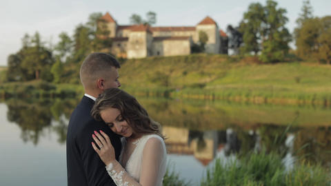 Caucasian groom with bride in the park near lake. Wedding couple. Newlyweds kiss Live Action