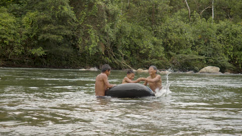 Indigenous Boys Are Playing In A Water With A Floating Tire In Ecuador Live Action