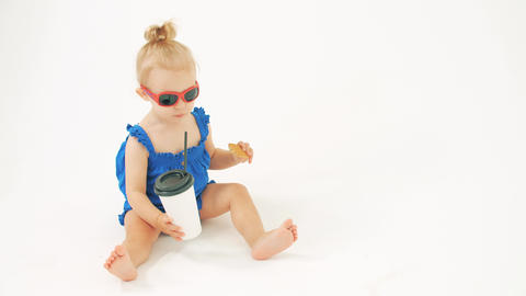 Cool baby girl wearing sunglasses drinks from paper cup with a straw against Live Action
