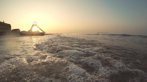 Sunrise by the sea. Catamaran stands on the beach by the sea. Sandy beach washed Footage