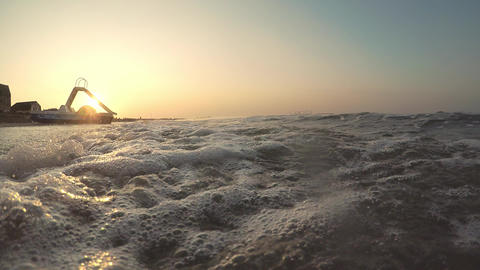 Sunrise by the sea. Catamaran stands on the beach by the sea. Sandy beach washed Live Action