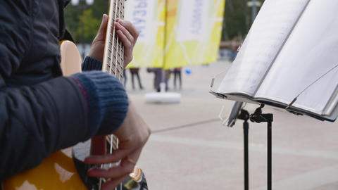 Person playing bass guitar outdoor Footage