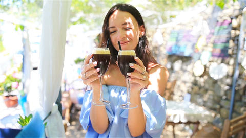 Woman in cafe drinking cold drinks smiling. Beautiful young female professional Footage