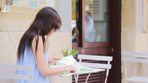 Young european woman with citymap in outdoors cafe. Portrait of attractive young Live Action