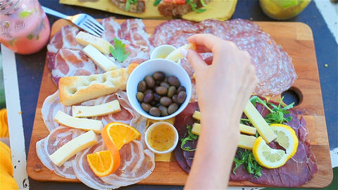 Tasty italian food. Fresh bruschettes, cheeses and meat on the board in outdoor Footage