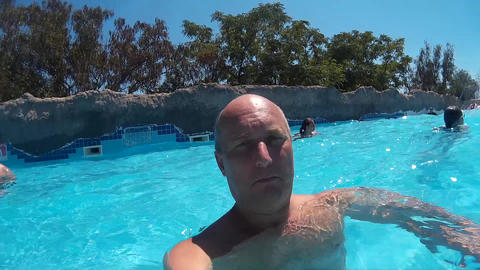 Bald man diving underwater swimming pool and blowing air bubble. Underwater view Footage