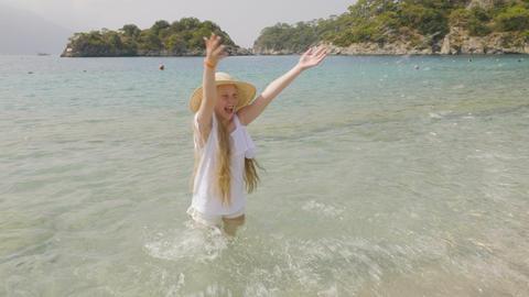 Carefree girl splashing sea water on paradise beach. Cheerful girl in straw hat Footage