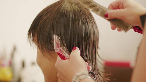 Hairdresser combing, parting woman's wet hair for haircut Footage