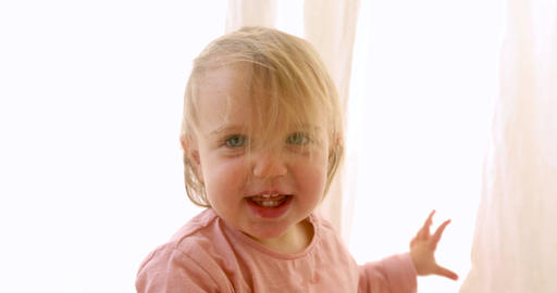 Cute little girl hiding behind a curtain Live Action
