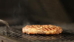 beef steak smokes deliciously on the grill.close-up Live Action