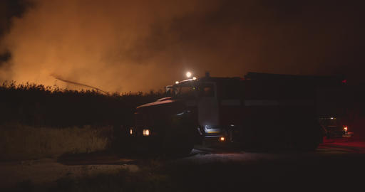 Fire truck with flashing lights on. Fire truck on background of burning grass on Live Action