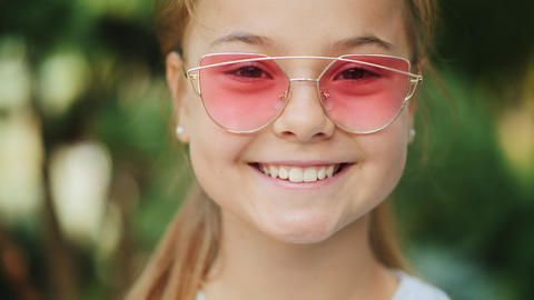 Young smiling girl in pink sunglasses outdoors, closeup Live Action