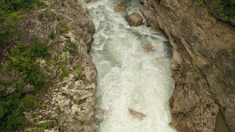 Aerial drone top view of a deep Hadzhokh Gorge and fast white stream of river Live Action