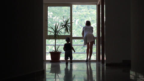 Small boy going to the large window to his mom, indoor back view, slow motion Footage