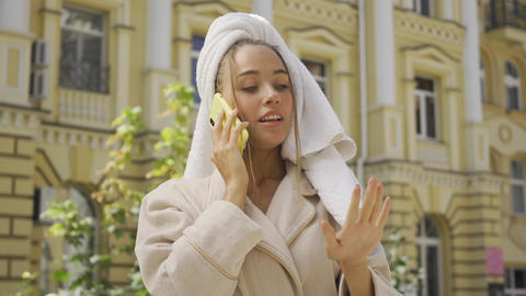 Portrait of cute young woman in bathrobe with towel on head talking by cellphone Live Action
