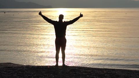 The man doing positive gesture with hand, thumbs up on the background of the sea Footage