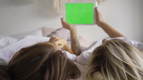 Two young girls in white t-shirts lying on the bed watching information on the Live Action