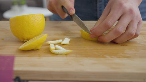Close-up hands of young woman separates the peel from a lemon with the sharp Live Action