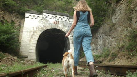 A girl stands on the background of the old tunnel. A girl with a dog is standing Live Action