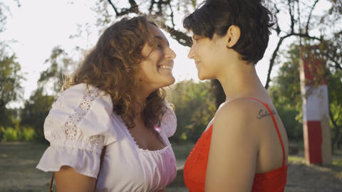 Portrait of two pretty women laughing and rubbing noses close-up. Beautiful Live Action