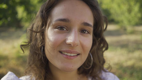 Close-up portrait of positive young woman with curly hair looking away and at Footage