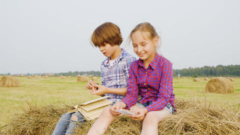 Teenager boy and girl sitting on haystack at countryside field. Carefree boy and Live Action