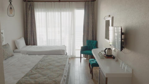 Cozy bedroom with comfortable beds and furniture in luxury resort. White bedroom Live Action