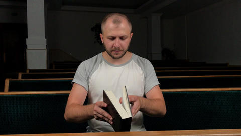 Holy Bible. Man preacher praying to God with his hands resting on a bible slow Live Action