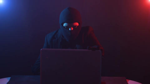 Angry computer hacker in suit stealing data from laptop illuminated by red and blue light Live Action
