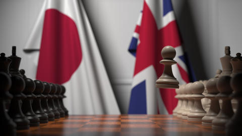 Flags of Japan and Great Britain behind chess board. The first pawn moves in the Live Action