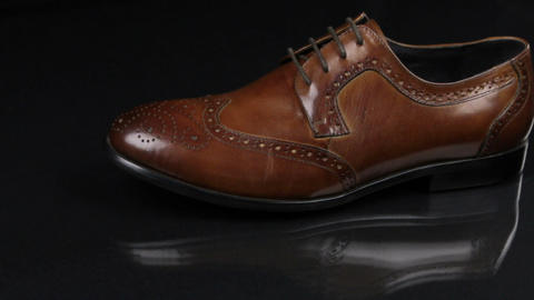 Elegant male shoes with laces stand on a black background with a beautiful Footage