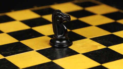 Rotation. Chess figure black horse on chess board. Close-up Footage
