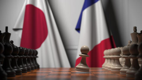 Flags of Japan and France behind chess board. The first pawn moves in the GIF
