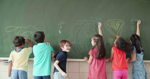 Multi-ethnic group of school children drawing on the chalkboard Live Action