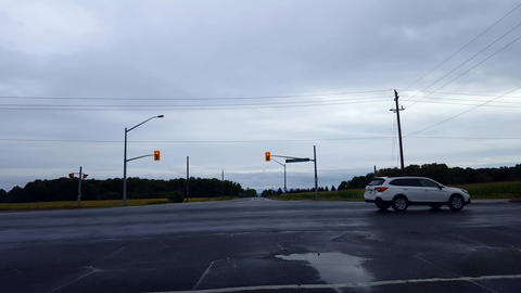 Driver Point of View POV Waiting at Red Light on Rural Road Under Overcast Sky. Traffic Passing Footage