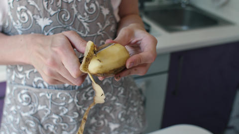Woman peeling potatoes at kitchen Live Action