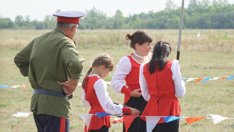 A man in a Cossack uniform talking to women in traditional Cossack clothes Live Action