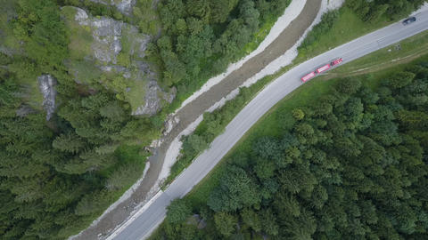 Excursion road train bus moves on a serpentine mountain road. Aerial view of a Live Action