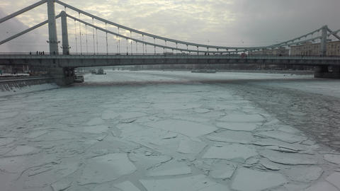 A frozen river surface and a bridge above it in the middle of a winter Footage
