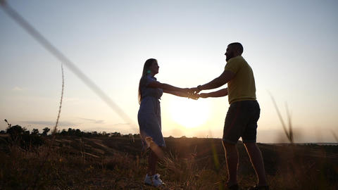 A love story of a young charming couple holding hands in rural landscape at Footage