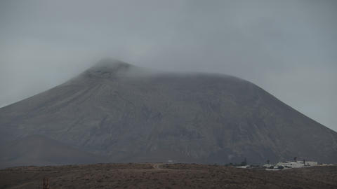 A peaceful view of a mountain with its top in the clouds Footage