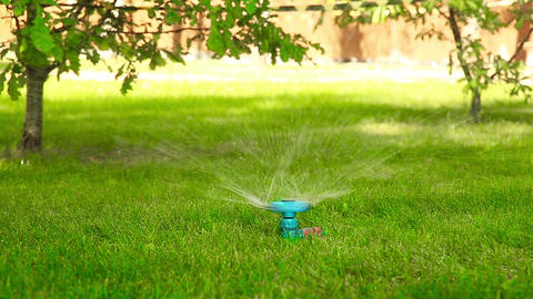 Rotating water sprayer on the lawn in motion HD Live Action