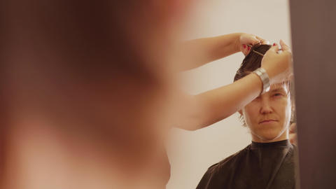 Woman face in mirror while hairdresser cutting her hair Live Action