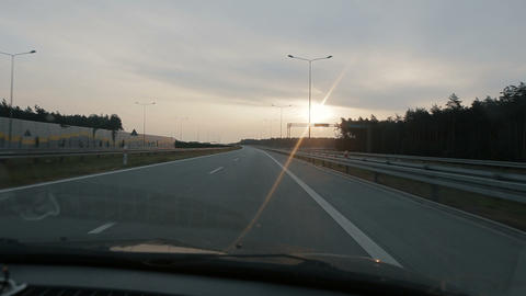 POV driving along a wide empty morning road early in the morning during sunrise Live Action