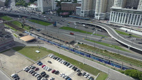An aerial view of a busy highway next to the railway station and urban buildings Footage